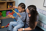 Education Childcare 2-3 year olds SEIT working with boy in classroom music activity