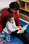 Education preschool 4 year olds books and reading female teacher sitting and reading to girl vertical