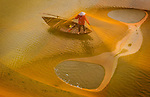 Fisherman works beneath golden nets by Ngoc Diem