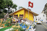 Switzerland. Canton of Neuchâtel. Neuchâtel. Grape Harvest Festival. The flower parade (corso) with its creative vehicles. A chalet, a swiss flag and some goats. An old man and two children, a boy and a girl, greet and wave their hands to the Public. Two men play the traditional Alps horns in front of fake white snowy mountains. © 2006 Didier Ruef