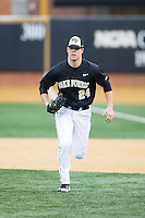 Wake Forest Demon Deacons first baseman Gavin Sheets (24) charges a bunt against the Appalachian State Mountaineers at Wake Forest Baseball Park on February 13, 2015 in Winston-Salem, North Carolina.  The Mountaineers defeated the Demon Deacons 10-1.  (Brian Westerholt/Four Seam Images)