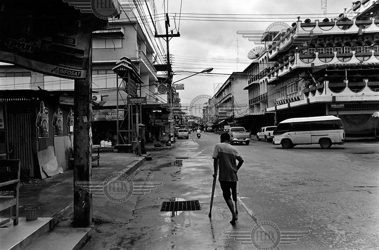 U Ko Oo, a former Burmese soldier who lost his leg to a mine in 1990, walking down a street in Mae Sot, Thailand, where he is sleeping rough. .