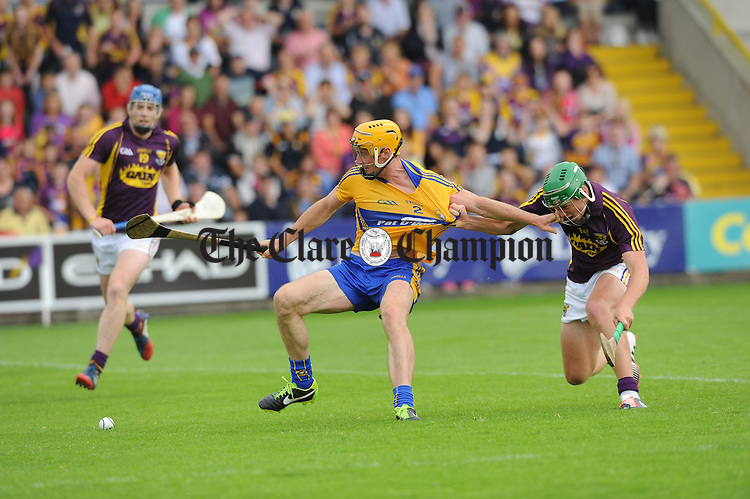 Cian Dillon of Clare in action against Conor Mc Donald of Wexford during their All-Ireland qualifier replay at Wexford Park. Photograph by John Kelly.