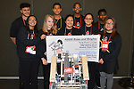 Knights and Roses at the VEX robotics competition in their team t-shirts holding the banner they brought to the competition.