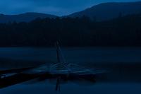 Boats at night blur during a long exposure on Shirakomaike Lake, Yatsugatake Range, Nagano, Japan.