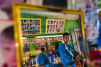 A young Bolivian hairdresser charges his customer for a haircut in a barber shop in El Alto, Bolivia, 11 February 2014.