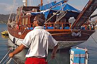 - Portoferraio (Island of Elba), sailor of the tourist port moors great sailing boat caique ....- Portoferraio (Isola d'Elba), marinaio del porto turistico ormeggia grande barca a vela caicco
