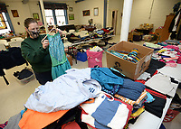 Jennifer Foster of the West Fork Community Church sorts clothing Thursday, Jan. 7, 2021, while setting up for the church's monthly Country Store planned for 8 a.m. to 1 p.m. Saturday. Since the 1950s, the Country Store is held on the second Saturday of the month . Visitors can receive free clothing, shoes and toys with other items and food available for a suggested donation. Money raised supports the church's outreach missions. Visit nwaonline.com/210108Daily/ for today's photo gallery. <br /> (NWA Democrat-Gazette/Andy Shupe)