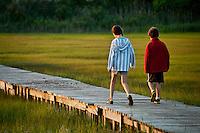 Kids walking on a boardwalk path through a salt marsh.