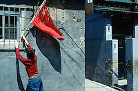 """China. Province of Beijing. Beijing. A young boy fixes near the public conveniences for men and women a chinese flag in a small alley of an old traditional town's quarter, called """"Hutong"""". Chinese flag is on display for the feast of the first of may.  © 2004 Didier Ruef"""