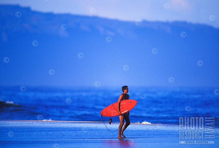 Surfer walking on the sandbar near pipeline, north shore Oahu