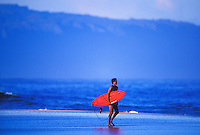 Surfer walking on the sandbar near pipeline, north shore Oahu
