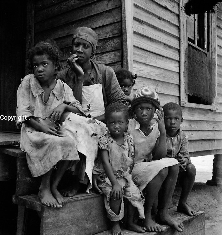 A Dollar a Day: Turpentine worker's family near Cordele, Alabama. Father's wages one dollar a day. This is the standard of living the turpentine trees support July 1936.<br /> <br /> Photo by Dorothea Lange.