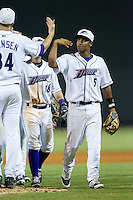 Cleuluis Rondon (5) of the Winston-Salem Dash slaps hands with teammate Kyle Hansen (34) following their victory over the Frederick Keys at BB&T Ballpark on July 29, 2014 in Winston-Salem, North Carolina.  The Dash defeated the Keys 4-0.   (Brian Westerholt/Four Seam Images)