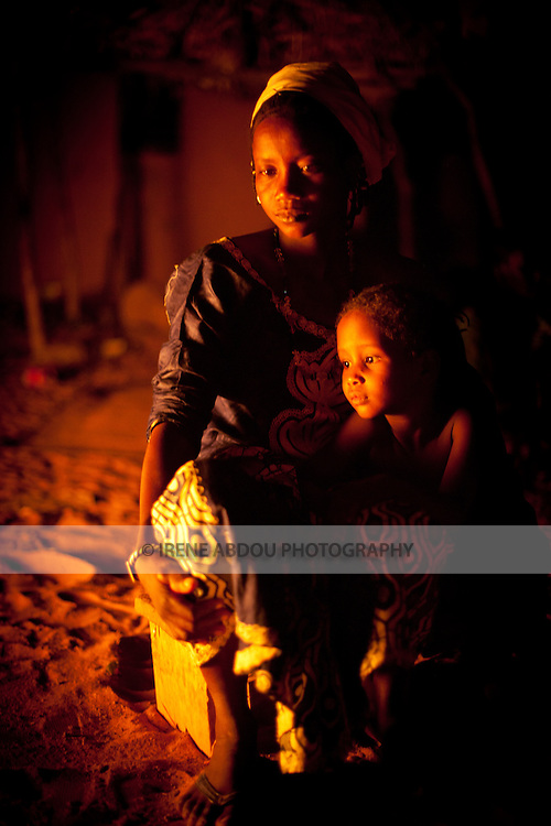 A woman and child sit next to the Tabaski fire.  Tabaski (Eid-Al-Adha) is Muslim West Africa's largest holiday and is celebrated with the biggest feast of the year.  Traditionally, each family slaughters one or more goats or sheep, which are roasted whole by the fire throughout the day.  Among this family in Djibo in northern Burkina Faso, the men got a late start to the barbecue, and the meat continues roasting into the night.