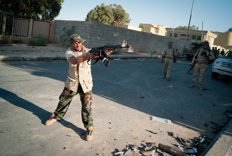 Anti-Gaddafi fighter exchanges fire with Gaddafi loyalists in Sirte, Libya.