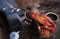 INDIA, Narmada, woman in village cooks Dal bhat , lentil soup and local bread