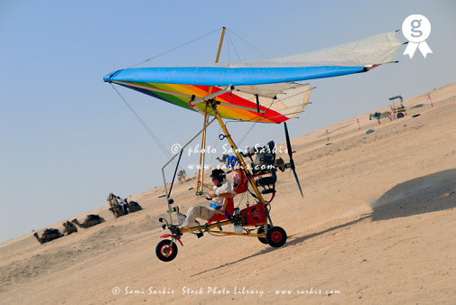 Microlite plane with two passengers landing in Sahara desert, side view (Licence this image exclusively with Getty: http://www.gettyimages.com/detail/sb10065474dy-001 )