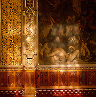 Dappled light from the stained glass windows shines on a Daniel Maclise fresco in the Royal Gallery illuminating the gilded carving