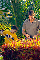 Father and son enjoying working on lawn in tropical setting