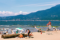 People sunbathing at Third Beach, Stanley Park at English Bay, Vancouver, BC, British Columbia, Canada, Summer - West Vancouver and North Shore Mountains in background