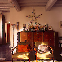 A country sitting room with a painted beamed ceiling. The room is furnished with two 1950's style armchairs placed in front of a Deco style sideboard.