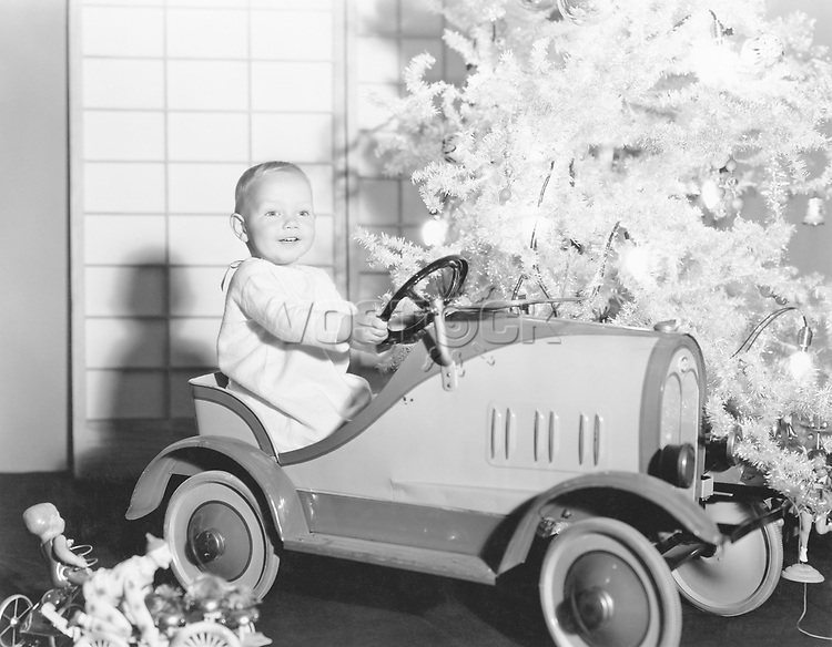 Child with toy car under Christmas tree