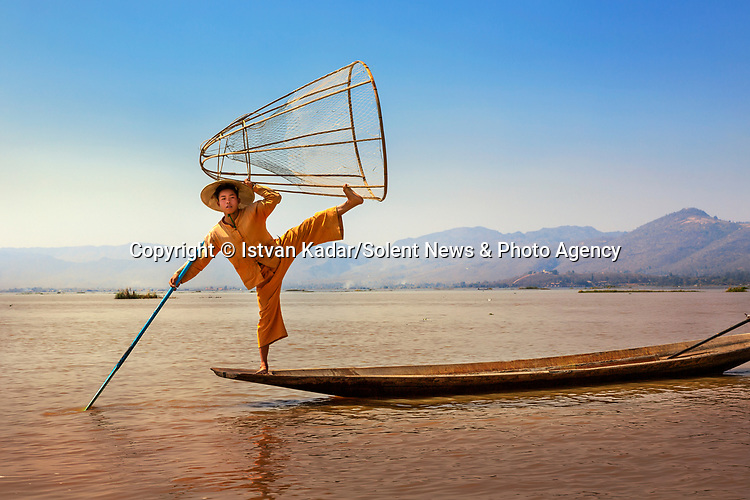 "A fisherman balances precariously on the edge of his boat on Inle Lake, Myanmar, demonstrating a technique dating back to the 12th century.<br /> <br /> The image was captured by photographer Istvan Kadar who said, ""This lake in Myanmar is famous for rowers masterfully balancing on one leg.  Photos of such hardworking fishermen are plentiful, but most are staged.  Of course, there are many ""real"" fishermen plying Inle Lake with traps in order to bring home the catch to their families.""<br /> <br /> ""The 'model' guys have figured out another way to make a few dollars off the lake—posing for tourists for tips.  They wear traditional, colourful clothing and perform amazing acrobatic shows; their sense of balance and the strength required to pose is quite remarkable.""<br /> <br /> Please byline: Istvan Kadar/Solent News<br /> <br /> © Istvan Kadar/Solent News & Photo Agency<br /> UK +44 (0) 2380 458800"
