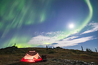 The aurora borealis, also called the northern lights, swirls over a tent camp the foothills surrounding Fairbanks, Alaska.