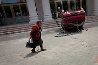 A Uighur woman passes a car overturned during riots. Ethnic violence between the Uighur and Han Chinese people had erupted in the city a few days earlier.