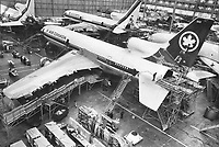 A Lockheed Tristar wearing Air Canada's colors is surrounded by scaffolding as workmen complete some of the final stages in a huge assembly hangar at Palmdale, California. The 256-passenger jet, to be delivered to Air Canada next month, is one of at least 10 TriStars slated for Air Canada over the next three years. In the background are other TriStars being built for other airlines. The three-engine plane is described as the world's quietest jetliner.<br /> <br /> Photo : Boris Spremo - Toronto Star archives - AQP