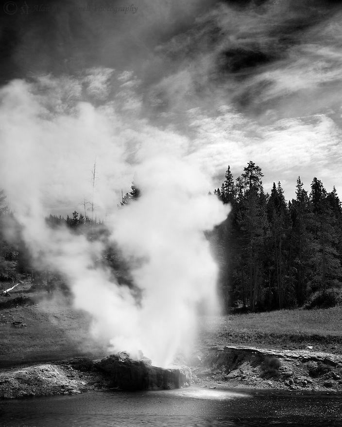 The Riverside Geyser, one of many in the Upper Geyser Basin of Yellowstone, erupts next to the Firehole River.  This one, along with others, helps give the river it's name.
