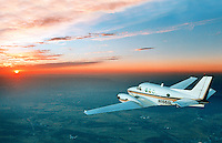 A small twin engine commuter plane flies into the beautiful orange sunset
