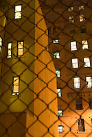 AVAILABLE FROM JEFF A S A FINE ART PRINT.<br /> <br /> AVAILABLE FROM PLAINPICTURE FOR COMMERCIAL AND EDITORIAL LICENSING.  Please go to www.plainpicture.com and search for image # p5690018.<br /> <br /> Urban Scene - Illuminated Windows in Building at Night, viewed thru chain link fence, Fulton Ferry neighborhood of Brooklyn, New York City, New York State, USA