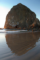 Haystack Rock in Cannon Beach, OR reflected in water with sand ripples visible at low tide during sunset