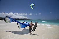 Kite surfer carrying his equipment rig (kite and board) down Kailua Beach