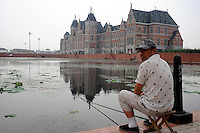 A man fishes for 40 Rmb a day at a lake in front of one of a copy of the Hague's International Court of Justice in Holland Village, a 600 acre re-creation of a Dutch city on the outskirts of Shenyang lies in ruins as a monument to corruption in China. Yang, a Dutch passport, got hooked on Holland while studying horticulture at Leiden University. Yang, who built the village with some of ill gotten millions, now languishes in jail and the town that is composed of several monumental buildings, plus windmills, artificial lakes, canals, a fullsize sailing ship, 1400 luxury apartments and even an indoor beach.