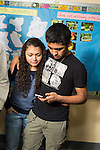 High school couple checking phone in corridor.