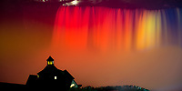 Amazing Niagara Falls night view with its water lit up in yellow and orange and with Table Rock Welcome Center in the foreground, USA and Canada
