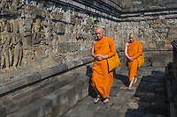 Borobudur, Java, Indonesia.  Buddhist Monks Performing Pradaksina, Circumambulating the Stupa in a Clockwise Direction, Gradually Ascending to the Topmost Level.  They also demonstrate shashu, one hand closed in a fist while the other grasps or covers the fist.