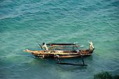 Zanzibar, Tanzania. Two men in an outrigger canoe.
