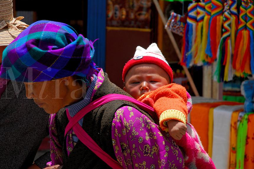 Tibetan woman carrying child on the Barkhor pilgrim circuit around the Jokhang Temple, Lhasa, Tibet.