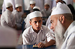 Islamic Studies teacher Qari Manzoor with students at the Jamianaeemia school which is a branch of the Bareldi sect of Sufi Islam in Lahore, Pakistan. The schools principal Sarfraz Ahmed Naeemi is part of an alliance formed by several moderate religious clerics to support the Pakistani Government in its fight against the Taliban in Swat and is teaching its new ideas in the schools.