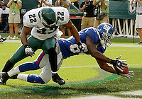 New York Giants wide receiver Tim Carver (R) recovers the football and beats Philadelphia Eagles defender Joselio Hanson (L) into the end zone for a touchdown in the fourth quarter in a NFL game in Philadelphia, Spetember 17, 2006. The Giants beat the eagles 30-24. REUTERS/Bradley C Bower (UNITED STATES)