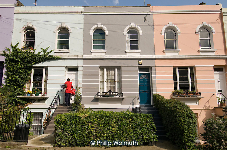 A postman delivers mail to brightly painted Victorian terrace houses in Camden Town