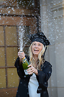 Kaylea Stevens, a University of Arkansas senior from Rock Wall, Texas, laughs Thursday, Nov. 19, 2020, as she sprays champagne in her mortar board and graduation gown while taking photographs on the university campus in Fayetteville. Stevens is set to graduate in December and does not plan return to in-person instruction on campus after the Thanksgiving break because of the pandemic. Visit nwaonline.com/201120Daily/ for today's photo gallery. <br /> (NWA Democrat-Gazette/Andy Shupe)