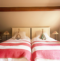 A country bedroom for a boy and a girl, decorated in neutral tones with a beamed ceiling. The room has two single beds with red and white striped covers. Soft toys sit are propped up against pillows against the painted headboards.