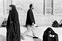 Iraq. Najaf. A man walks by a group of Iraqi women near the entrance to the mosque, Holy Shrine of Imam Ali. The women wear the abaya and the hidjab (islamic headscarf) on their heads to cover their hair. The abaya, sometimes also called aba, is a simple, loose over-garment, essentially a robe-like dress, worn by some women in parts of the Islamic world. Traditional abaya are black and may be either a large square of fabric draped from the shoulders or head or a long caftan. The abaya covers the whole body except the face, feet, and hands. The word hijab (or hidjab) refers to both the veil covering the head and traditionally worn by muslim women (Islamic headscarf), but also the  modest muslim styles of dress in general. Imam Ali was the cousin and son-in-law of the Islamic prophet Muhammad and was the first male convert to Islam. Shias regard Ali as the first Imam and consider him and his descendants the rightful successors to Muhammad. 26.02.04 © 2004 Didier Ruef .