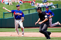 Jason Christian (16) of the Midland RockHounds tries not to hit Umpire Stu Scheurwater as he throws to first base during a game against the Springfield Cardinals on April 19, 2011 at Hammons Field in Springfield, Missouri.  Photo By David Welker/Four Seam Images
