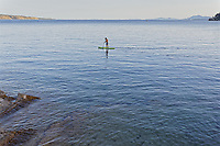 Pictured: A paddleboarder off Kerasia beach in Corfu, Greece. <br /> Re: A 27-year-old British man drowned while swimming off Kerasia beach,  in Corfu, Greece. <br /> The unidentified man, was seen swimming several hundred feet from the shore in northeastern Corfu, when he was seen struggling in the water. <br /> Witnesses said locals jumped in the sea to save him and dragged the man to shore.